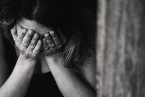 counselling for anxiety that causes woman to hide her face behind her hands after experiencing an anxiety attack