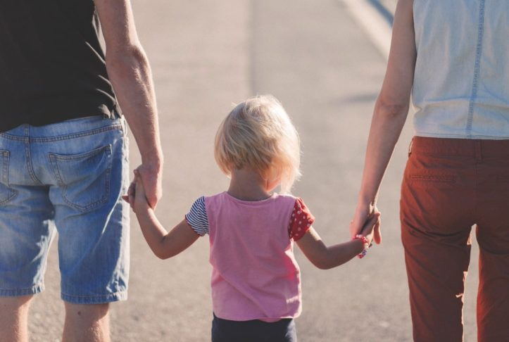 Child-holding-her-parents-hands-feeling-secure