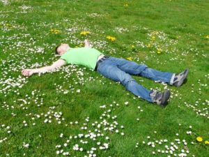 man-lying-on-grass-field-practising-mindfulness