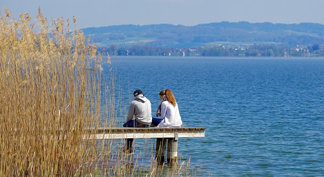 two people sitting down talking on jetty